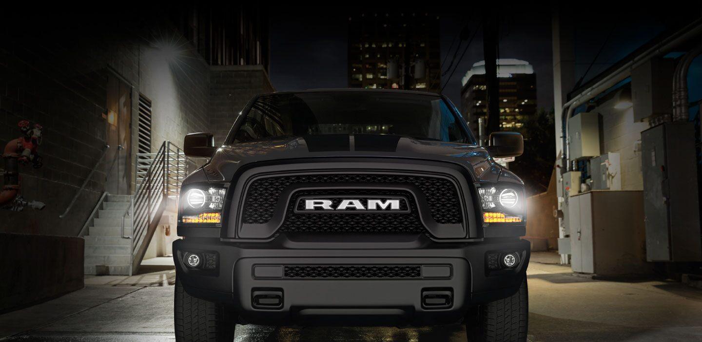 Ram 1500 Classic Warlock color Granite Crystal estacionada en un depósito con los faros delanteros encendidos.