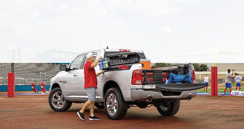 Un hombre carga bebidas en la RamBox de la Ram1500 Classic Laramie. La puerta trasera está abierta y se observa gran cantidad de equipos en la plataforma.