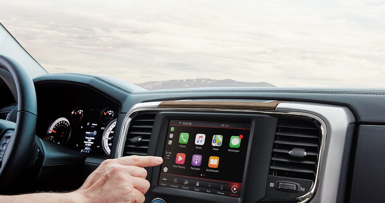 Pantalla táctil de Uconnect y una mano que se acerca a las selecciones en pantalla de Apple CarPlay.