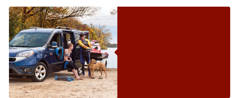Un hombre y una mujer se ponen trajes de buceo junto a una wagon para pasajeros Ram ProMaster City 2020 en la playa.