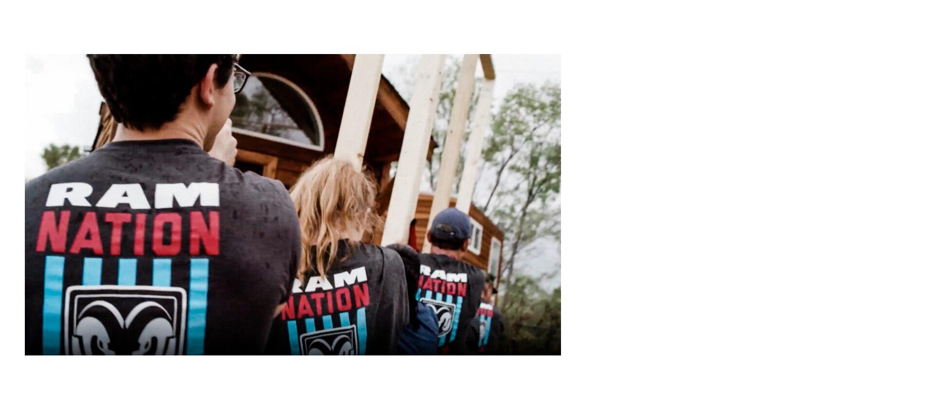 Voluntarios de Ram Nation trabajando juntos para elevar la estructura de una casa.