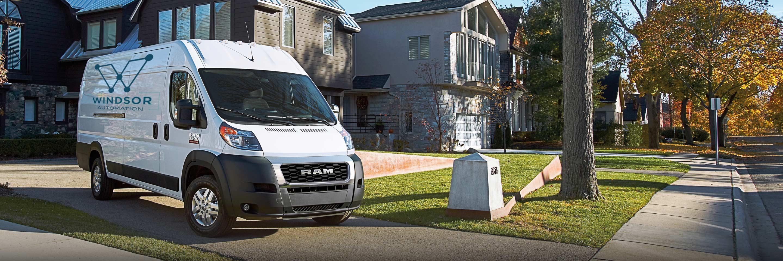 Una cargo vanRam ProMaster35002020 estacionada en una entrada, en la calle de un barrio. Logo de la cabeza de Ram y temporada de la camioneta comercial.