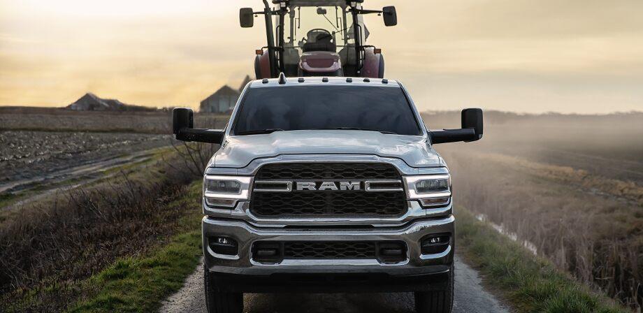 Se muestra una Ram 2500 Tradesman 2019 con el paquete de apariencia cromada, circulando por un camino de tierra cerca de una granja. Maquinaria agrícola pesada en la plataforma de la camioneta.