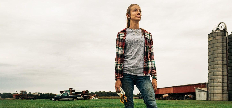 Grayce Emmick de pie orgullosa en su granja con su camioneta Ram en segundo plano.