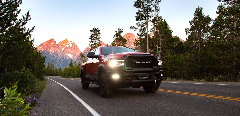Mostrar Una Ram 2500 Power Wagon 2019 andando por un camino de montaña.
