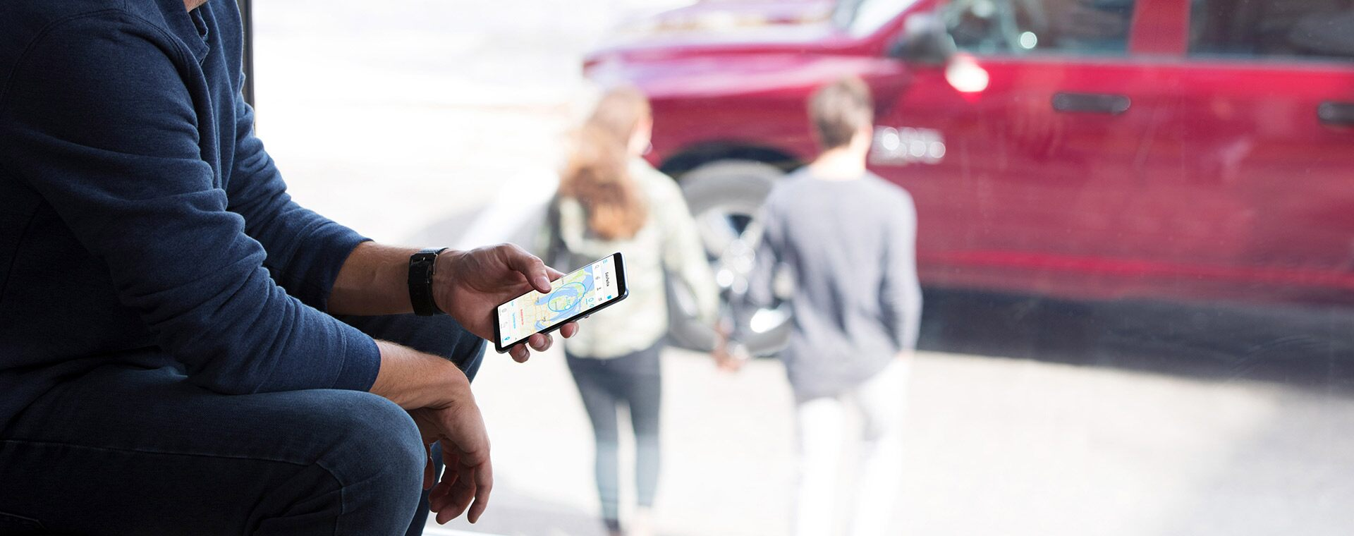 Un hombre sosteniendo un smartphone con un mapa en la pantalla.